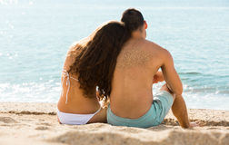 Loving pair relaxing on sand beach Royalty Free Stock Images