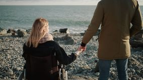 Loving pair is standing on seacoast, disabled woman and healthy man, back view stock footage