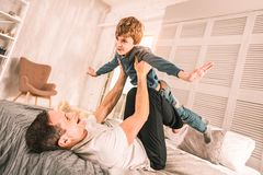 Loving parent carefully holding up his child above him. royalty free stock photos