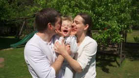 Loving parents embracing and kissing cute boy in summer garden. Handheld shot. Loving parents embracing and kissing cute boy in summer garden, front view stock video