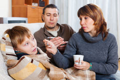 Loving parents giving medicinal syrup to teen son. At home. Focus on boy Stock Photos