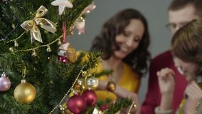 Loving parents helping their daughter to decorate Christmas tree, magic moments. Stock footage stock footage