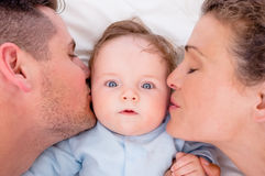 Loving parents kissing baby Royalty Free Stock Photos