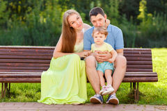 Loving parents with little girl on bench in park Royalty Free Stock Image