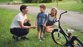 Loving parents are making surprise for little son closing his eyes and giving him new bicycle as present, happy boy is