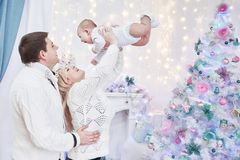 Loving parents with play with their baby standing in the festive living room. The concept of Christmas royalty free stock images