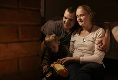 Loving parents playing with their young son. Loving parents sitting arm in arm near the fireplace playing with their young son and his colorful yellow plastic Royalty Free Stock Photo