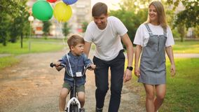Loving parents are teaching son cute boy to ride bike in city park, child is cycling and his father is holding him. Helping to balance while happy mother is stock video