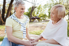Loving pensioners expressing love to each other outdoors. Feeling save with you. Cute happy retired couple expressing care while holding hands and enjoying Stock Images