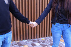 Loving people firmly hold hands and overcame each other, standin Royalty Free Stock Photography