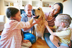 Loving pet. A young friendly family of four cuddling their pet stock photography