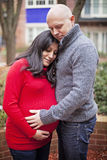 Loving Pregnant couple. A loving pregnant couple hugging in a city courtyard stock photo