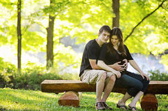 Loving pregnant couple. An affectionate young pregnant couple sitting on a bench stock images