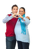 Loving pregnant couple forming heart royalty free stock image