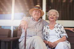 Loving retired couple relaxing on a bench outside their house Stock Images