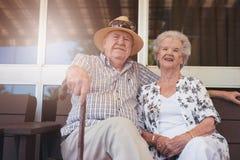 Loving retired couple relaxing on a bench outside their house. Portrait of loving retired couple relaxing on a bench outside their house. Caucasian elderly men Stock Images