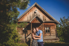 Loving romantic couple in the village, near a wooden house. Man embraces a young woman. Concept: love, romance, summer. Royalty Free Stock Image