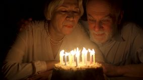 Loving senior couple celebrating anniversary with cake at home in the evening. Blowing out candles. Loving senior couple celebrating anniversary with cake at stock video footage
