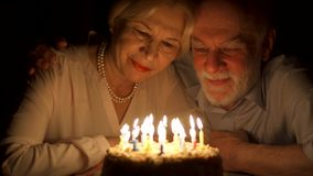 Loving senior couple celebrating anniversary with cake at home in the evening. Blowing out candles. Loving senior couple celebrating anniversary with cake at stock video