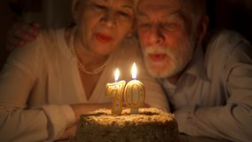 Loving senior couple celebrating 70s anniversary with cake at home in evening. Blowing out candles. Loving senior couple celebrating 70s anniversary with cake at stock video
