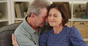 Loving senior couple cuddling on couch Royalty Free Stock Image