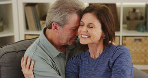 Loving senior couple cuddling on couch Stock Photography