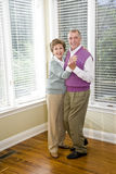 Loving senior couple dancing in living room Stock Image