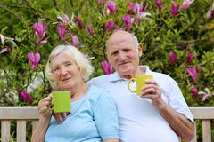 Loving senior couple drinking tea in the garden Stock Photo