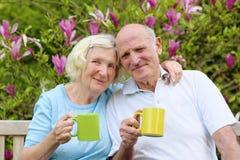 Loving senior couple drinking tea in the garden Royalty Free Stock Images