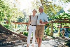 Loving senior couple enjoying a walk in the park Stock Photos