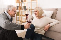 Loving senior couple enjoying wine at home royalty free stock photo