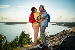 Loving senior couple hiking, standing on the top of rock Stock Photography