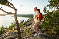 Loving senior couple hiking, standing on the top of rock Stock Images