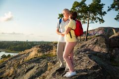 Loving senior couple hiking, standing on the top of rock Stock Image