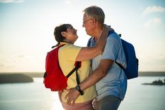 Loving senior couple hiking, standing on the top of rock Stock Photo