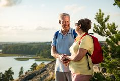 Loving senior couple hiking, standing on the top of rock Royalty Free Stock Photo