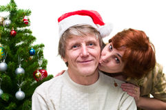 Loving senior couple are kissing. Mature woman kissing a old husband near the Christmas tree. Loving senior couple isolated on white background Stock Photography