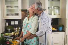 Loving senior couple kissing while cooking in kitchen. At home Stock Photography