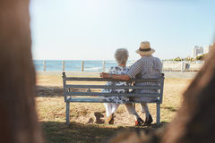 Loving senior couple relaxing on a bench at the seaside Royalty Free Stock Image
