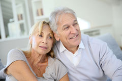Loving senior couple sitting at home relaxing. Senior couple looking towards the future Royalty Free Stock Photography
