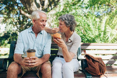 Loving senior couple sitting on a park bench. Having coffee and muffins. Tourist relaxing outdoors on a park bench Royalty Free Stock Photos