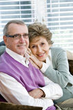 Loving senior couple sitting together on couch royalty free stock images