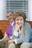 Loving senior couple sitting together on couch Royalty Free Stock Photo