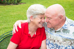 Loving Senior Couple Snuggling. Mature happy couple sitting outside, laughing and smiling, with man's arm around woman royalty free stock image