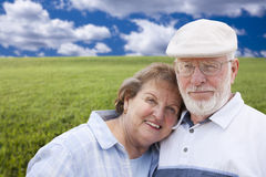 Loving Senior Couple Standing in Grass Field Stock Photos