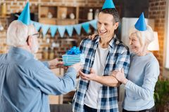 Loving senior father congratulating his adult son with birthday. Sincere congratulations. Caring elderly men giving a present to his son, congratulating him with Stock Photography