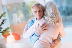 Loving senior husband embracing his wife. Love you to the moon and back. Extremely happy retired gentleman smiling with joy while hugging his wife tightly stock photography