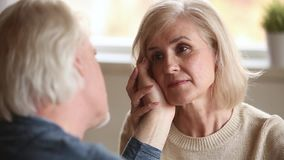 Loving senior husband stroking face of aged wife confessing love