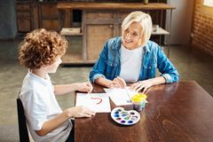 Loving senior lady chatting with grandson while both painting Royalty Free Stock Photo
