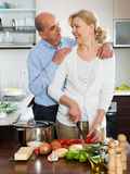 Loving senior with mature wife smiling and preparing vegetables Royalty Free Stock Photography